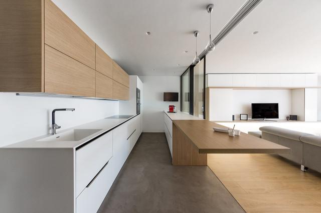 Foto de cocina lineal, contemporánea, grande, abierta, con fregadero integrado, armarios con paneles lisos, puertas de armario de madera clara, salpicadero blanco, electrodomésticos negros y península