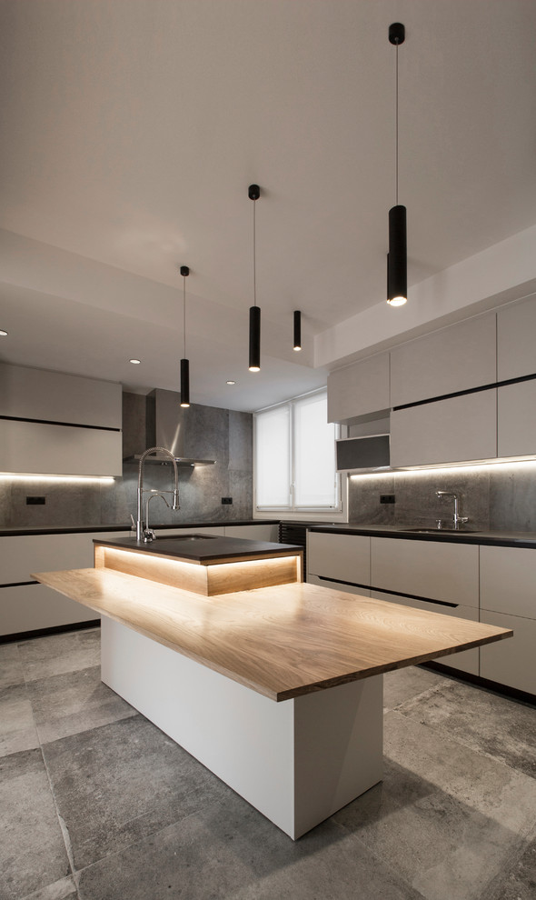 Trendy l-shaped ceramic tile and gray floor enclosed kitchen photo in Bilbao with flat-panel cabinets, gray backsplash, an island, black countertops, an undermount sink and gray cabinets