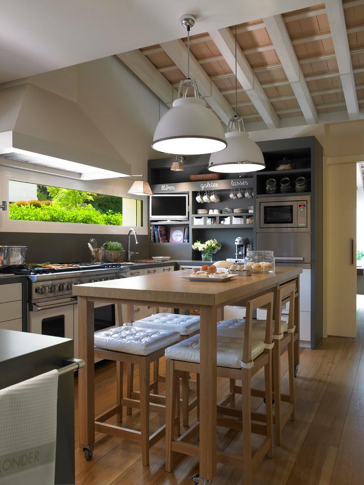 Foto de cocina comedor en U, contemporánea, de tamaño medio, con armarios abiertos, puertas de armario grises, salpicadero verde, electrodomésticos de acero inoxidable y suelo de madera en tonos medios