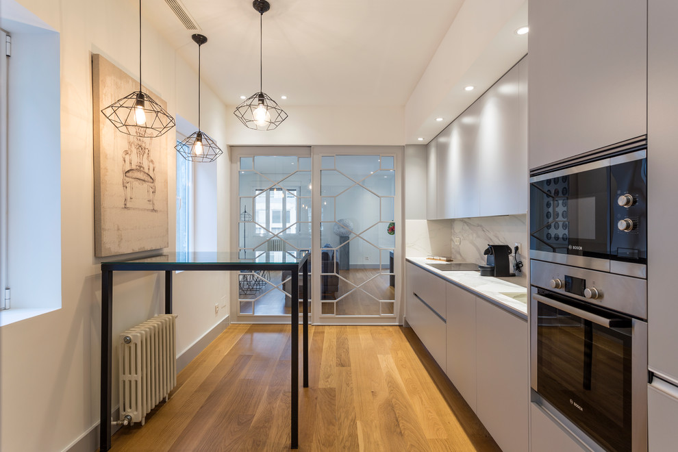 Kitchen - mid-sized contemporary single-wall medium tone wood floor kitchen idea in Madrid with flat-panel cabinets, gray cabinets, marble countertops, white backsplash, marble backsplash, stainless steel appliances and white countertops