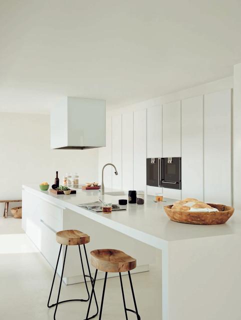 Modelo de cocina de galera, actual, grande, con fregadero integrado, armarios con paneles lisos, puertas de armario blancas, encimera de acrílico, una isla, electrodomésticos negros y encimeras blancas