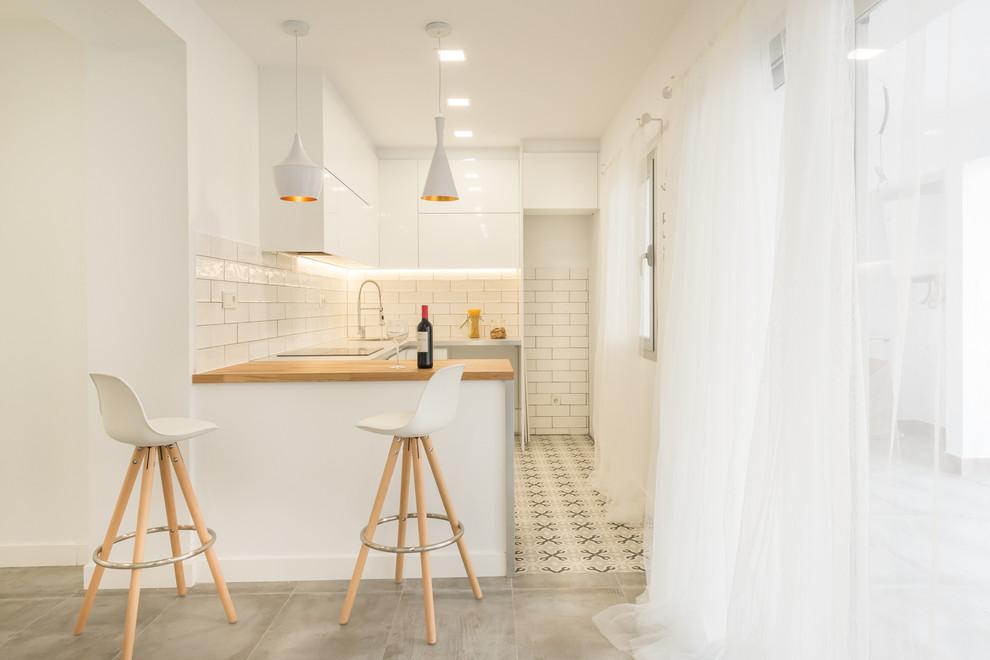 Foto de cocina en U, escandinava, pequeña, abierta, con armarios con paneles lisos, puertas de armario blancas, encimera de madera, suelo de baldosas de cerámica y península