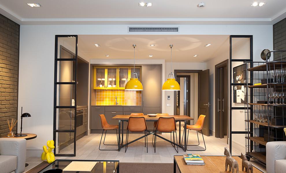 Foto de cocina comedor en L, contemporánea, de tamaño medio, sin isla, con armarios con paneles lisos, puertas de armario grises, salpicadero amarillo, salpicadero de azulejos de cerámica y suelo de madera clara