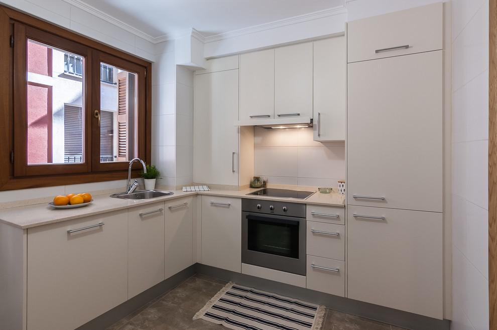 Imagen de cocinas en L contemporánea, sin isla, con fregadero encastrado, armarios con paneles lisos, puertas de armario blancas, salpicadero blanco, electrodomésticos con paneles, suelo gris y encimeras beige