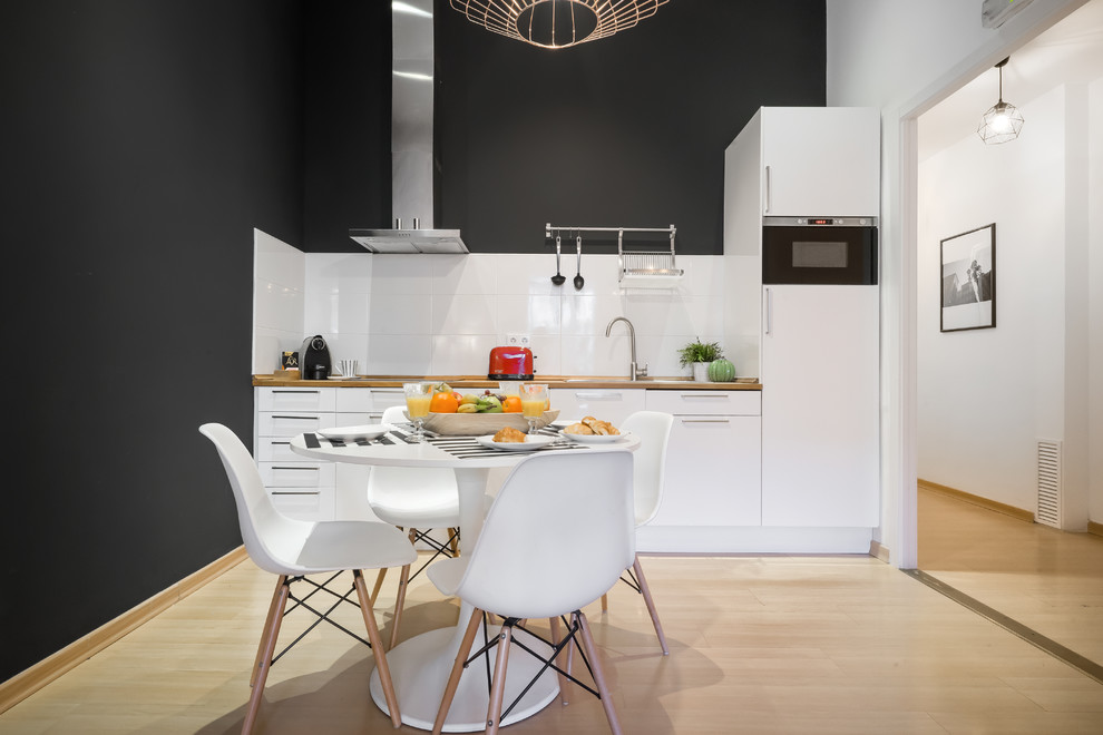 Eat-in kitchen - mid-sized contemporary single-wall light wood floor and beige floor eat-in kitchen idea in Barcelona with flat-panel cabinets, white cabinets, wood countertops, white backsplash, no island, brown countertops, a drop-in sink and paneled appliances