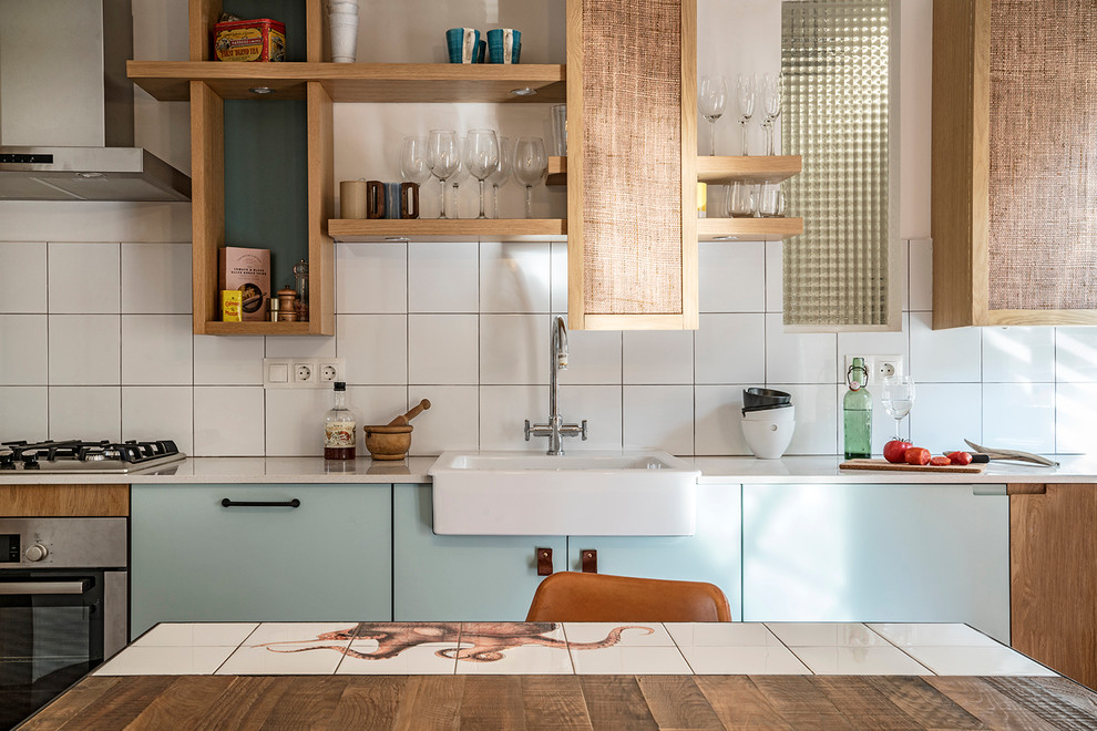 Inspiration for a small mediterranean single-wall concrete floor eat-in kitchen remodel in Barcelona with a single-bowl sink, open cabinets, blue cabinets, quartz countertops, white backsplash, ceramic backsplash, stainless steel appliances and no island