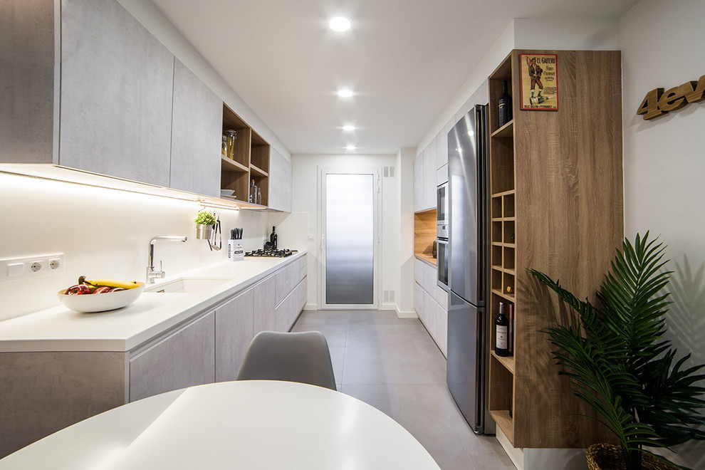 Example of a trendy galley gray floor eat-in kitchen design in Barcelona with flat-panel cabinets, white backsplash, no island, white countertops, an undermount sink, gray cabinets and stainless steel appliances