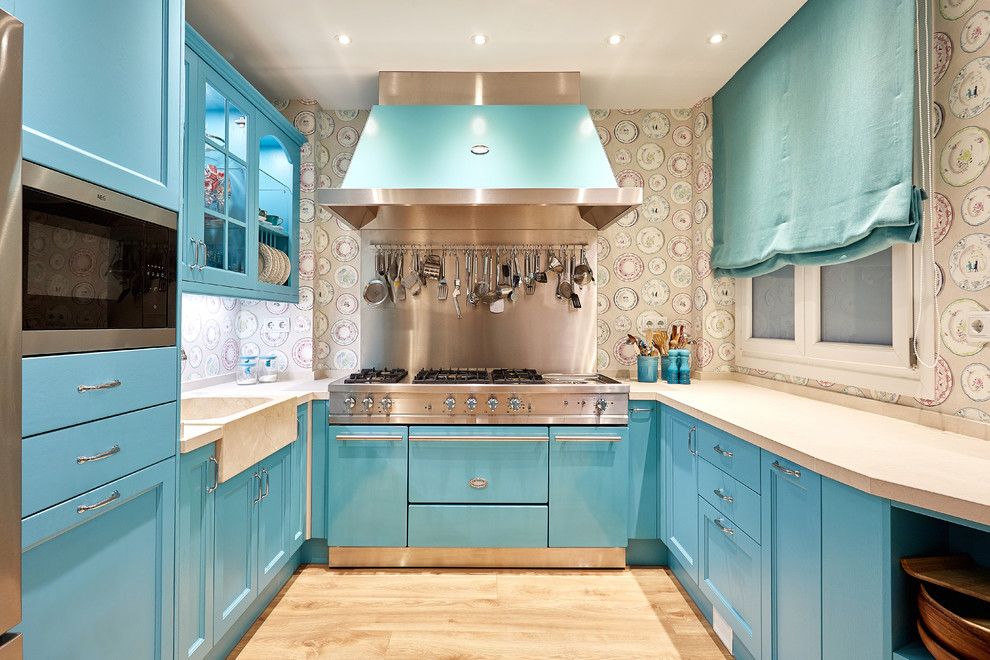 Mid-sized transitional u-shaped light wood floor and beige floor enclosed kitchen photo in Madrid with blue cabinets, multicolored backsplash and stainless steel appliances