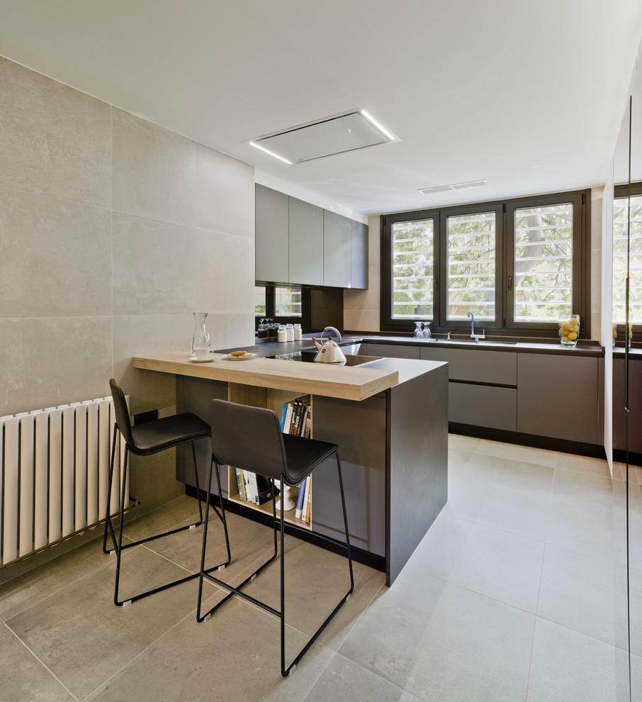 Foto de cocina en U, contemporánea, de tamaño medio, con armarios con paneles lisos, puertas de armario grises, península, suelo gris, encimera de madera y salpicadero negro