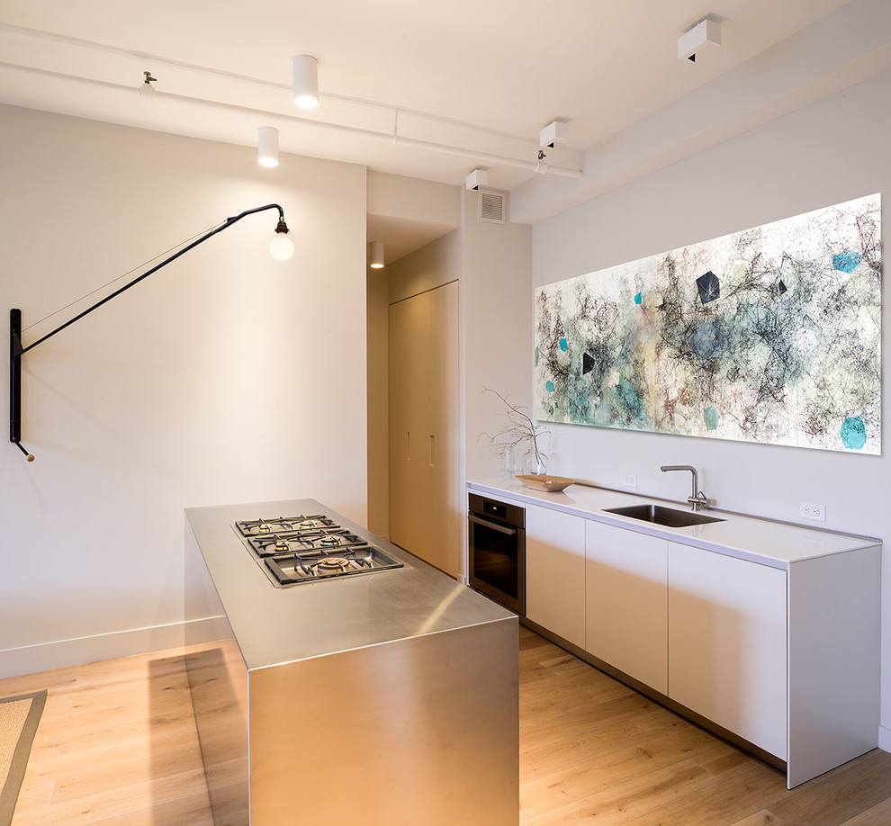 Inspiration for a small contemporary galley medium tone wood floor kitchen remodel in New York with an undermount sink, flat-panel cabinets, white cabinets, stainless steel countertops, stainless steel appliances and an island