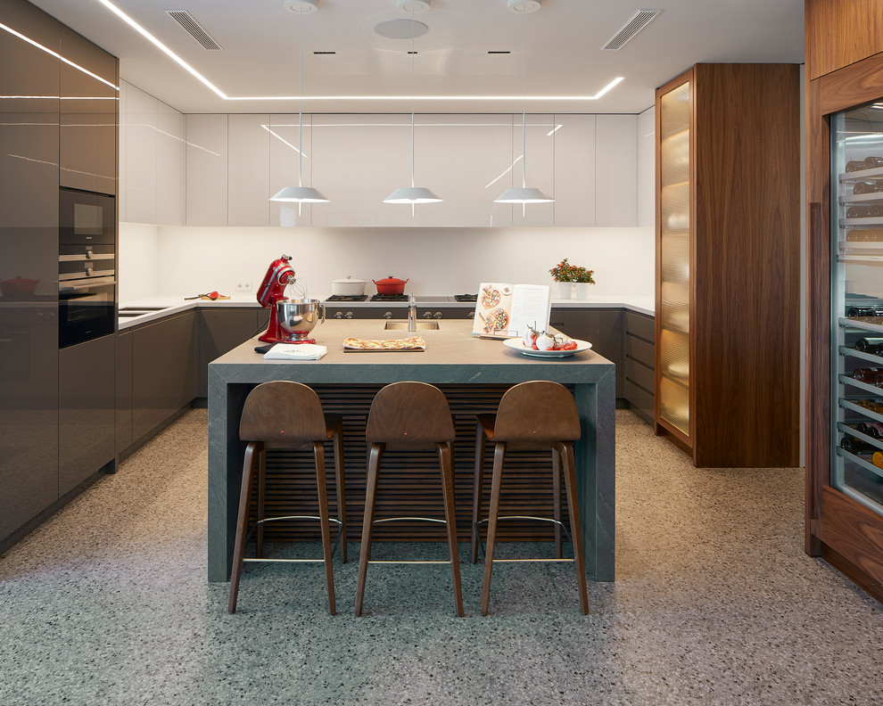 Trendy u-shaped gray floor kitchen photo in Other with an undermount sink, flat-panel cabinets, gray cabinets, white backsplash, an island and white countertops
