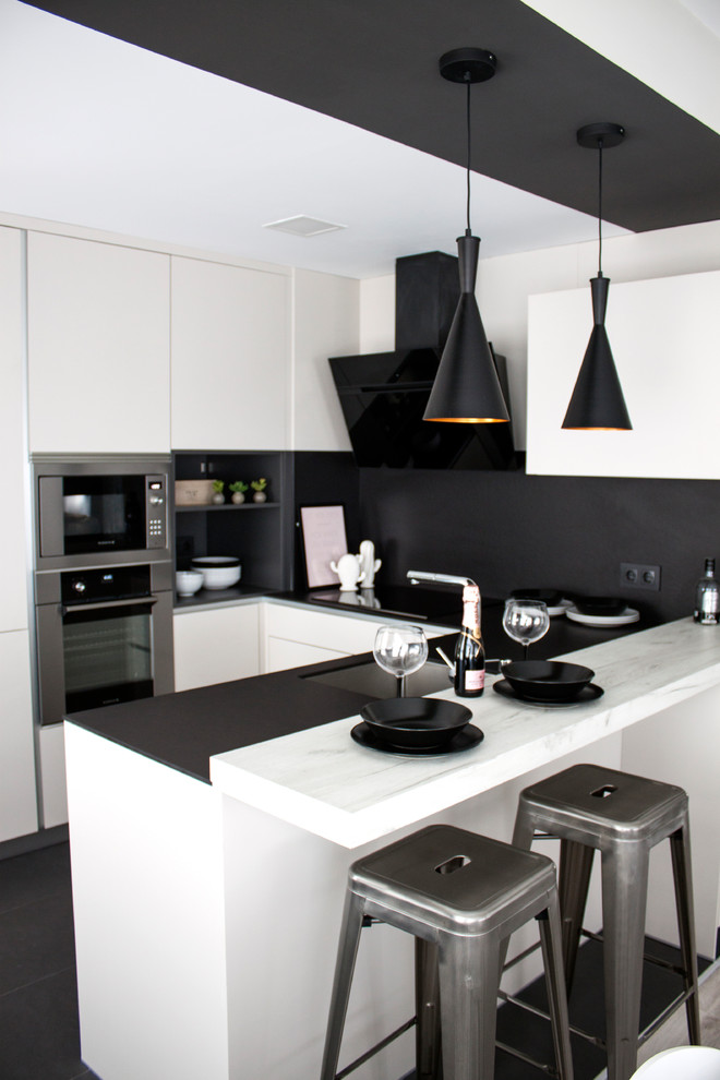 Kitchen - mid-sized modern u-shaped black floor kitchen idea in Madrid with flat-panel cabinets, white cabinets, marble countertops, black backsplash, a peninsula, an undermount sink and stainless steel appliances