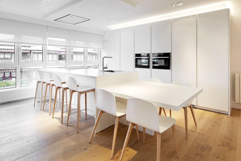 Foto de cocina lineal, contemporánea, grande, abierta, con fregadero de un seno, armarios con paneles lisos, puertas de armario blancas, suelo de madera en tonos medios y una isla