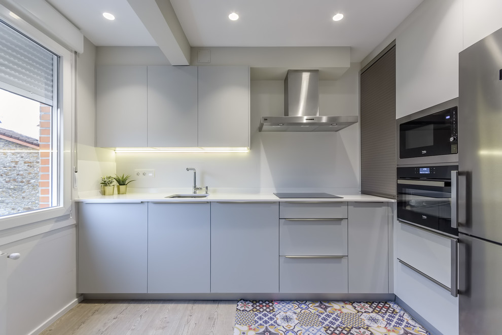 Trendy multicolored floor kitchen photo in Bilbao with an undermount sink, flat-panel cabinets, white backsplash, no island, white countertops, gray cabinets and stainless steel appliances