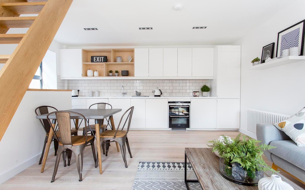 Inspiration for a mid-sized scandinavian single-wall light wood floor open concept kitchen remodel in Barcelona with flat-panel cabinets, white cabinets, white backsplash, subway tile backsplash, black appliances and no island