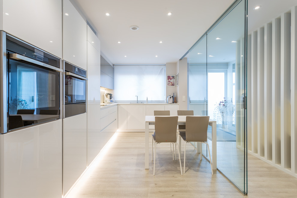 Trendy l-shaped light wood floor and beige floor eat-in kitchen photo in Other with an undermount sink, flat-panel cabinets, white cabinets, white backsplash, stainless steel appliances, no island and white countertops