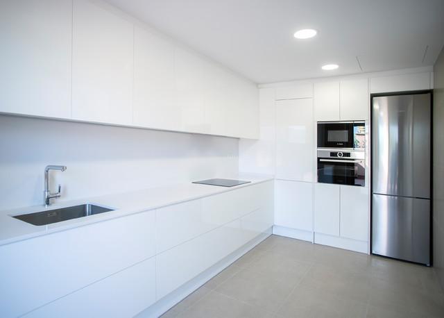 Diseño de cocina en L, contemporánea, grande, abierta, sin isla, con fregadero de un seno, puertas de armario blancas, salpicadero blanco, electrodomésticos de acero inoxidable, suelo de baldosas de cerámica, suelo beige y encimeras blancas