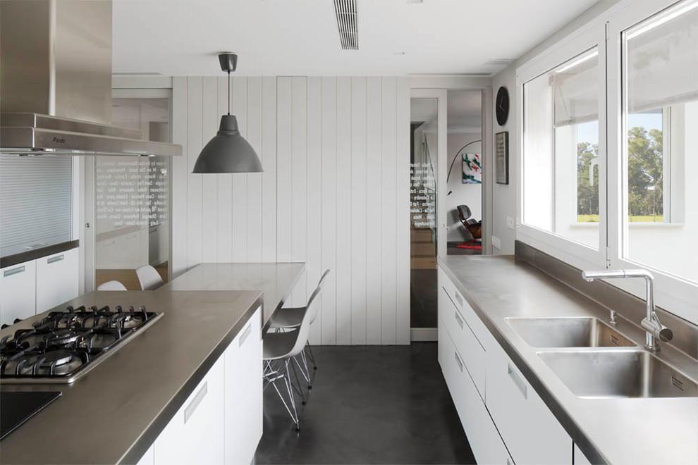 Ejemplo de cocina de galera, escandinava, grande, cerrada, con fregadero de doble seno, armarios con paneles lisos, puertas de armario blancas, encimera de acero inoxidable, electrodomésticos de acero inoxidable, suelo de cemento, una isla y encimeras grises