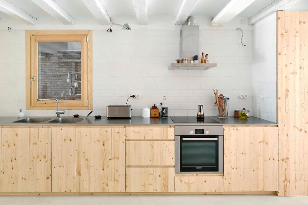Foto di una cucina lineare scandinava di medie dimensioni con lavello a doppia vasca, ante lisce, ante in legno chiaro, top in acciaio inossidabile, paraspruzzi bianco, paraspruzzi con piastrelle diamantate, elettrodomestici in acciaio inossidabile e nessuna isola