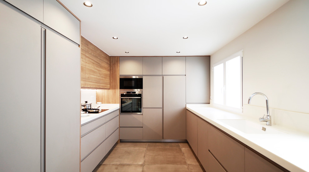 Enclosed kitchen - large modern u-shaped concrete floor and beige floor enclosed kitchen idea in Other with an integrated sink, flat-panel cabinets, gray cabinets, white backsplash, no island, white countertops and paneled appliances