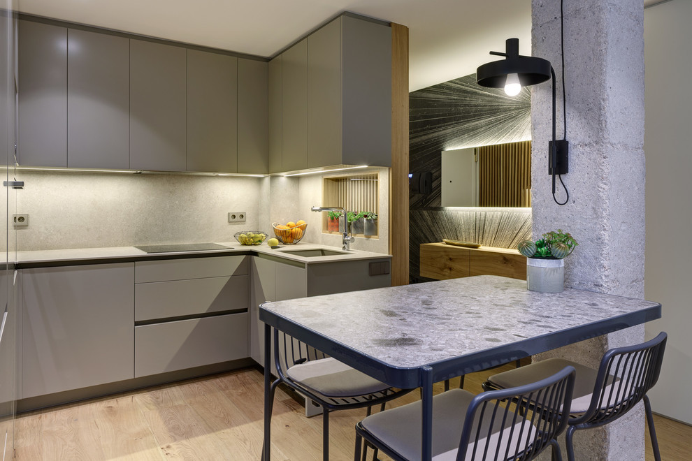 Mid-sized trendy u-shaped light wood floor and beige floor eat-in kitchen photo in Alicante-Costa Blanca with an undermount sink, flat-panel cabinets, gray cabinets, gray backsplash, gray countertops, paneled appliances and no island