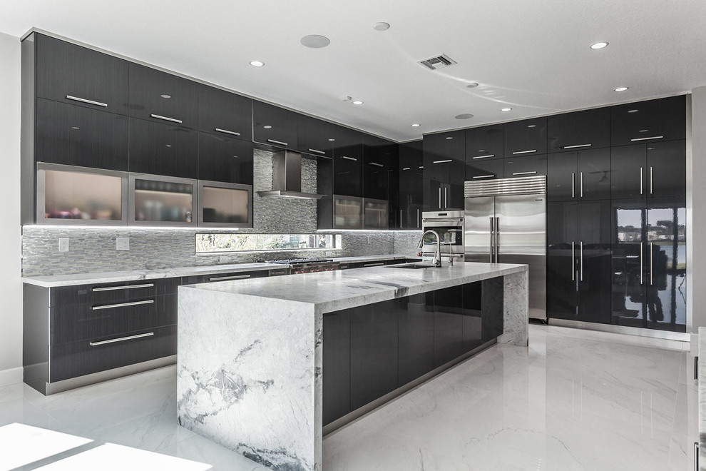 Huge trendy l-shaped ceramic floor and white floor kitchen photo with an undermount sink, flat-panel cabinets, metallic backsplash, stainless steel appliances, an island, gray countertops, black cabinets and mosaic tile backsplash