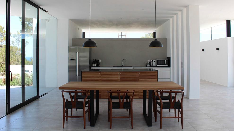 Ejemplo de cocina comedor lineal, moderna, con electrodomésticos de acero inoxidable, una isla, suelo gris, encimeras negras, armarios con paneles lisos, puertas de armario blancas y salpicadero verde