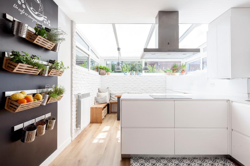 Diseño de cocina actual, de tamaño medio, con armarios con paneles lisos, puertas de armario blancas, península, suelo de madera clara, suelo beige y salpicadero blanco