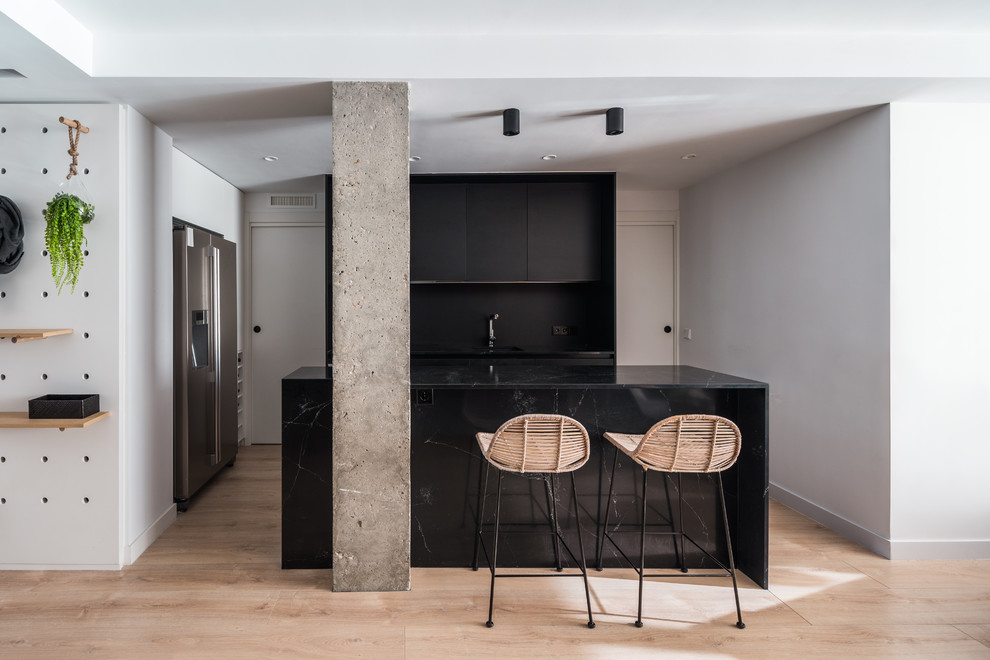 Inspiration for a contemporary l-shaped light wood floor and beige floor eat-in kitchen remodel in Other with an undermount sink, flat-panel cabinets, black cabinets, black backsplash, stainless steel appliances, an island and black countertops