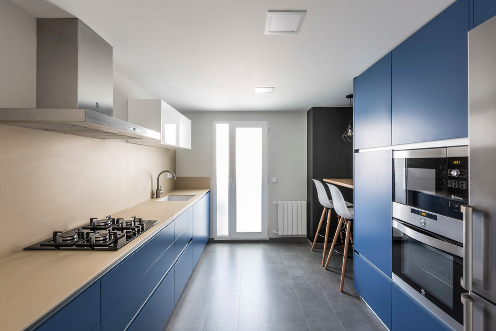 Example of a trendy galley gray floor kitchen design in Valencia with an undermount sink, flat-panel cabinets, blue cabinets, beige backsplash and stainless steel appliances