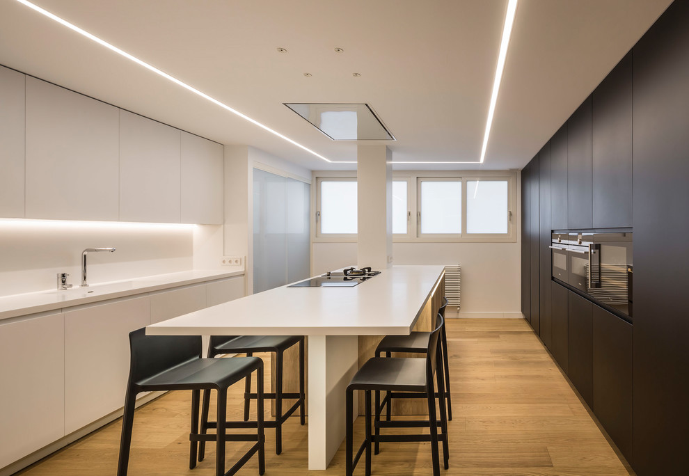 Kitchen - large contemporary light wood floor kitchen idea in Valencia with an integrated sink, flat-panel cabinets, white cabinets, quartz countertops, white backsplash, black appliances, an island and white countertops