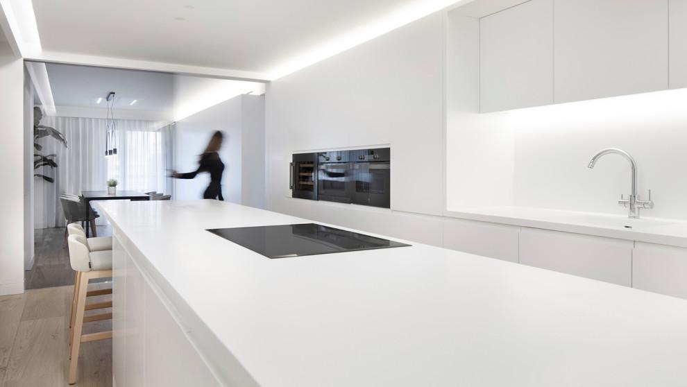 Modelo de cocina moderna, extra grande, abierta, con armarios con paneles lisos, puertas de armario blancas, encimera de cuarzo compacto, salpicadero blanco, suelo de baldosas de cerámica, una isla, suelo beige, encimeras blancas, fregadero bajoencimera y electrodomésticos negros