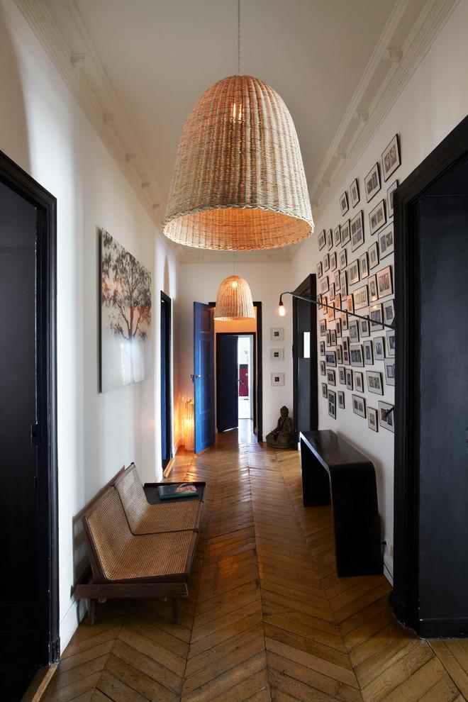 Diseño de recibidores y pasillos actuales, grandes, con paredes blancas y suelo de madera en tonos medios