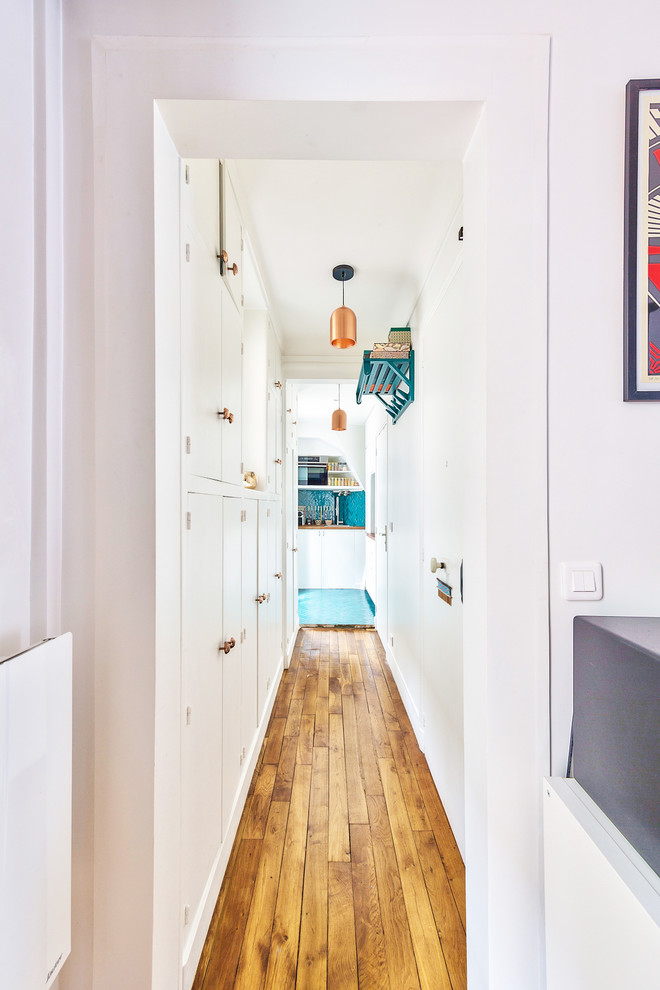 Imagen de recibidores y pasillos retro, de tamaño medio, con paredes blancas, suelo de madera en tonos medios y suelo marrón
