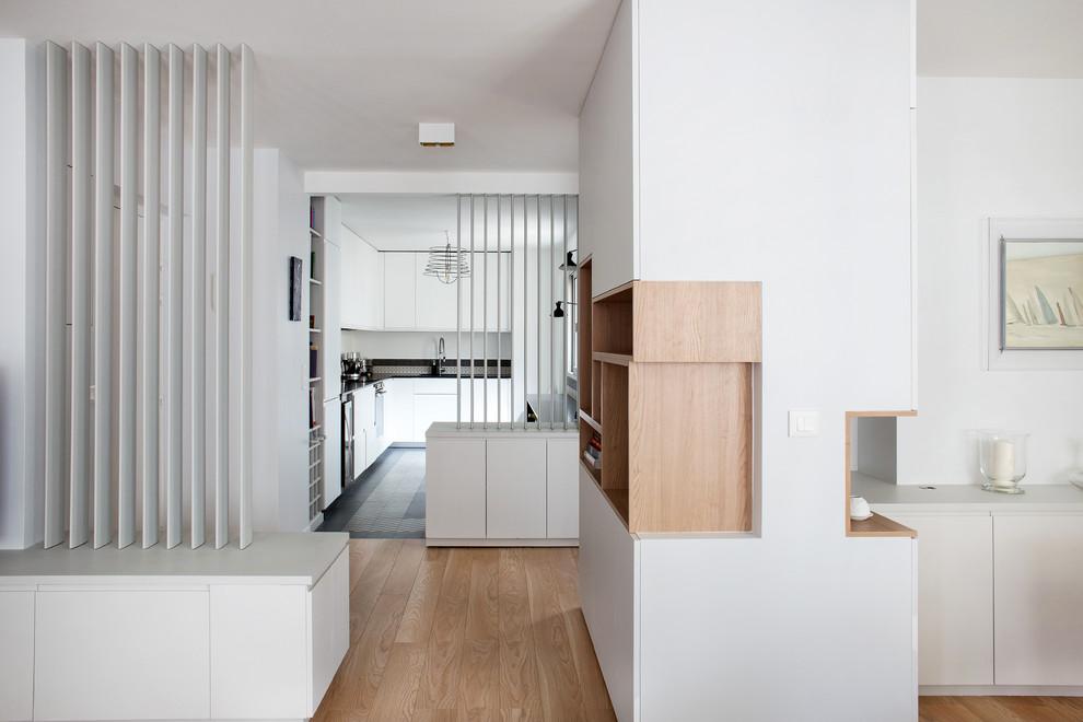 Inspiration pour un couloir design de taille moyenne avec un mur blanc et un sol en bois brun.