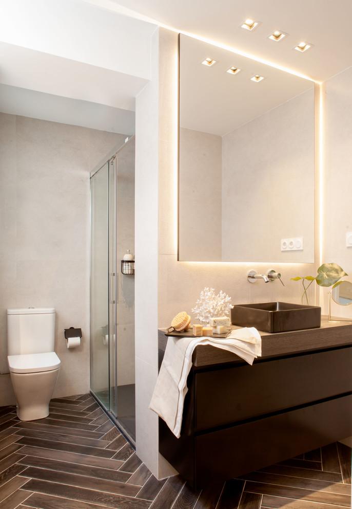 Diseño de cuarto de baño actual con armarios con paneles lisos, puertas de armario de madera en tonos medios, ducha empotrada, paredes grises, lavabo sobreencimera, encimera de madera, suelo marrón, ducha con puerta corredera y encimeras marrones