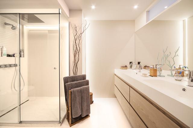 Idee per una stanza da bagno con doccia design di medie dimensioni con ante lisce, ante in legno scuro, doccia ad angolo, lavabo integrato, porta doccia scorrevole, pareti bianche e pavimento bianco