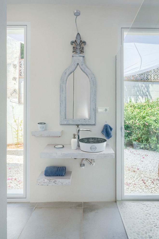 Inspiration for a mid-sized mediterranean master gray floor bathroom remodel in Other with white walls, a vessel sink, wood countertops and white countertops