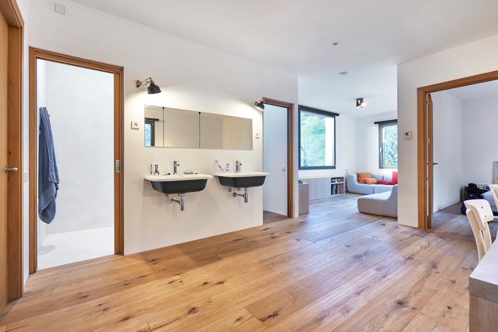 Modelo de cuarto de baño actual con paredes blancas, suelo de madera en tonos medios, lavabo suspendido y suelo marrón