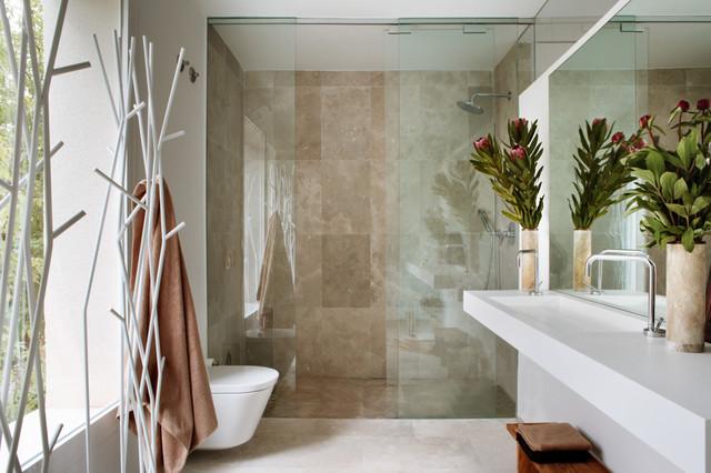 Imagen de cuarto de baño con ducha, actual, de tamaño medio, con ducha empotrada, sanitario de pared, baldosas y/o azulejos de piedra, paredes blancas, suelo de travertino, lavabo de seno grande y encimera de acrílico