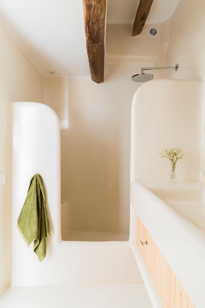 Diseño de cuarto de baño con ducha, mediterráneo, con armarios con paneles lisos, puertas de armario de madera clara, ducha empotrada, lavabo de seno grande, ducha abierta, paredes beige y suelo beige