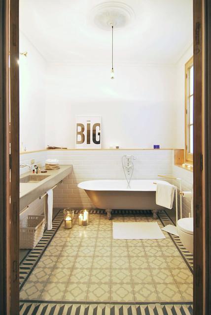 Diseño de cuarto de baño con ducha, mediterráneo, de tamaño medio, con bañera con patas, baldosas y/o azulejos blancos, paredes blancas, sanitario de una pieza, baldosas y/o azulejos de cemento, suelo con mosaicos de baldosas, lavabo integrado, encimera de cemento y combinación de ducha y bañera
