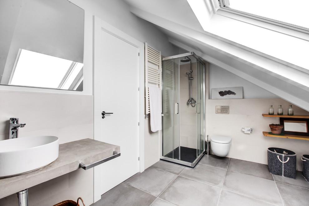 Diseño de cuarto de baño con ducha, actual, con baldosas y/o azulejos grises, lavabo sobreencimera, ducha con puerta corredera, ducha esquinera, sanitario de pared, paredes beige, encimera de cemento, suelo gris y encimeras grises
