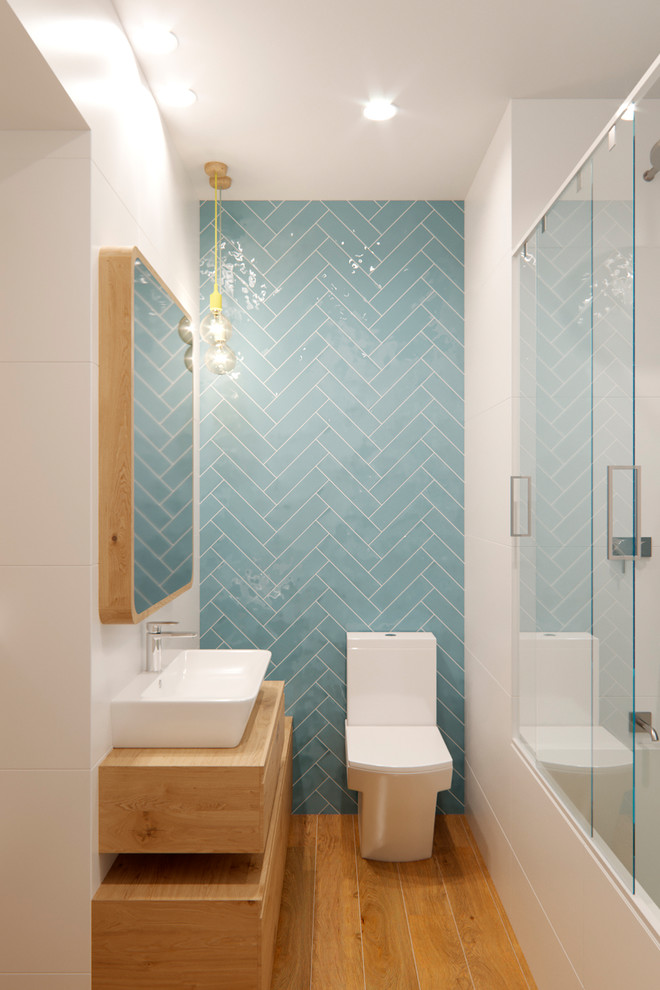 Example of a small danish 3/4 blue tile and ceramic tile medium tone wood floor and beige floor bathroom design in Barcelona with light wood cabinets, white walls, wood countertops, flat-panel cabinets, a one-piece toilet, a vessel sink and beige countertops