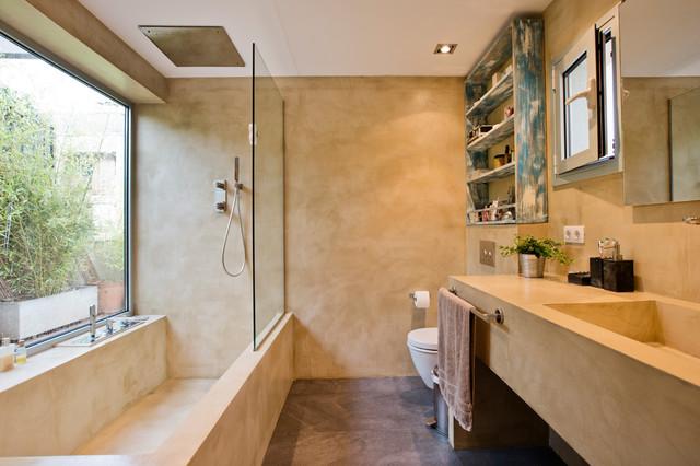 Foto de cuarto de baño actual con puertas de armario beige, combinación de ducha y bañera, lavabo integrado, bañera esquinera, paredes beige, suelo de cemento, suelo marrón, ducha abierta y encimeras beige