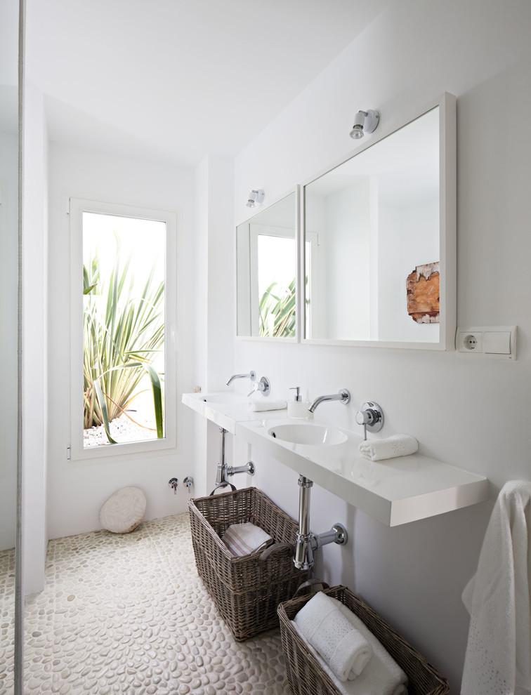 Ejemplo de cuarto de baño con ducha, mediterráneo, de tamaño medio, con paredes blancas, suelo de baldosas tipo guijarro, lavabo suspendido y encimera de acrílico