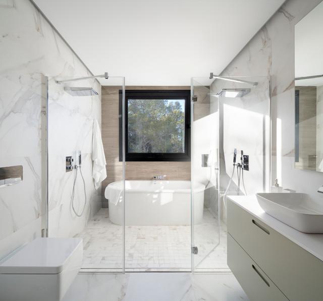 Imagen de cuarto de baño principal, contemporáneo, grande, con armarios con paneles lisos, puertas de armario blancas, bañera exenta, ducha doble, sanitario de pared, paredes blancas, lavabo sobreencimera y ducha con puerta con bisagras