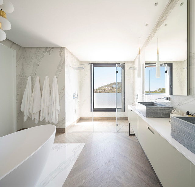 This is an example of an expansive contemporary ensuite bathroom in Bilbao with flat-panel cabinets, white cabinets, a freestanding bath, a double shower, white walls, medium hardwood flooring, a vessel sink and a hinged door.