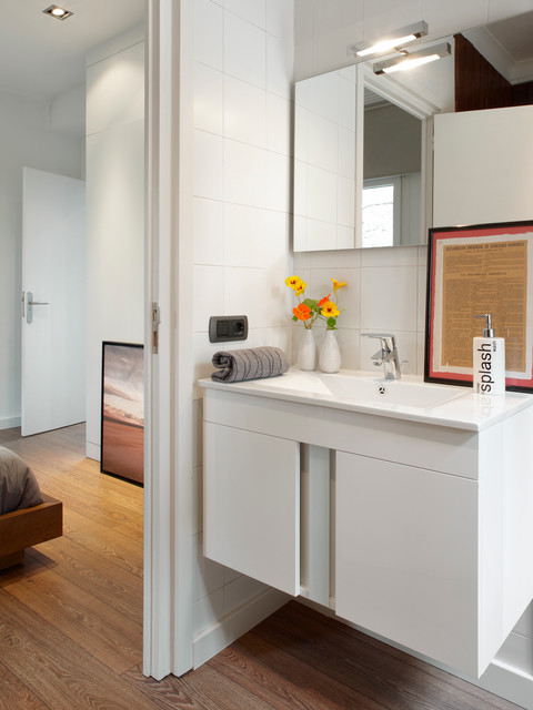 Photo of a mid-sized contemporary 3/4 bathroom in Barcelona with flat-panel cabinets, white cabinets, white tile, white walls, medium hardwood floors and a wall-mount sink.