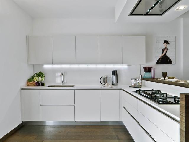 Foto di una cucina design di medie dimensioni con lavello sottopiano, ante lisce, ante bianche, top in superficie solida, paraspruzzi bianco e pavimento in legno massello medio